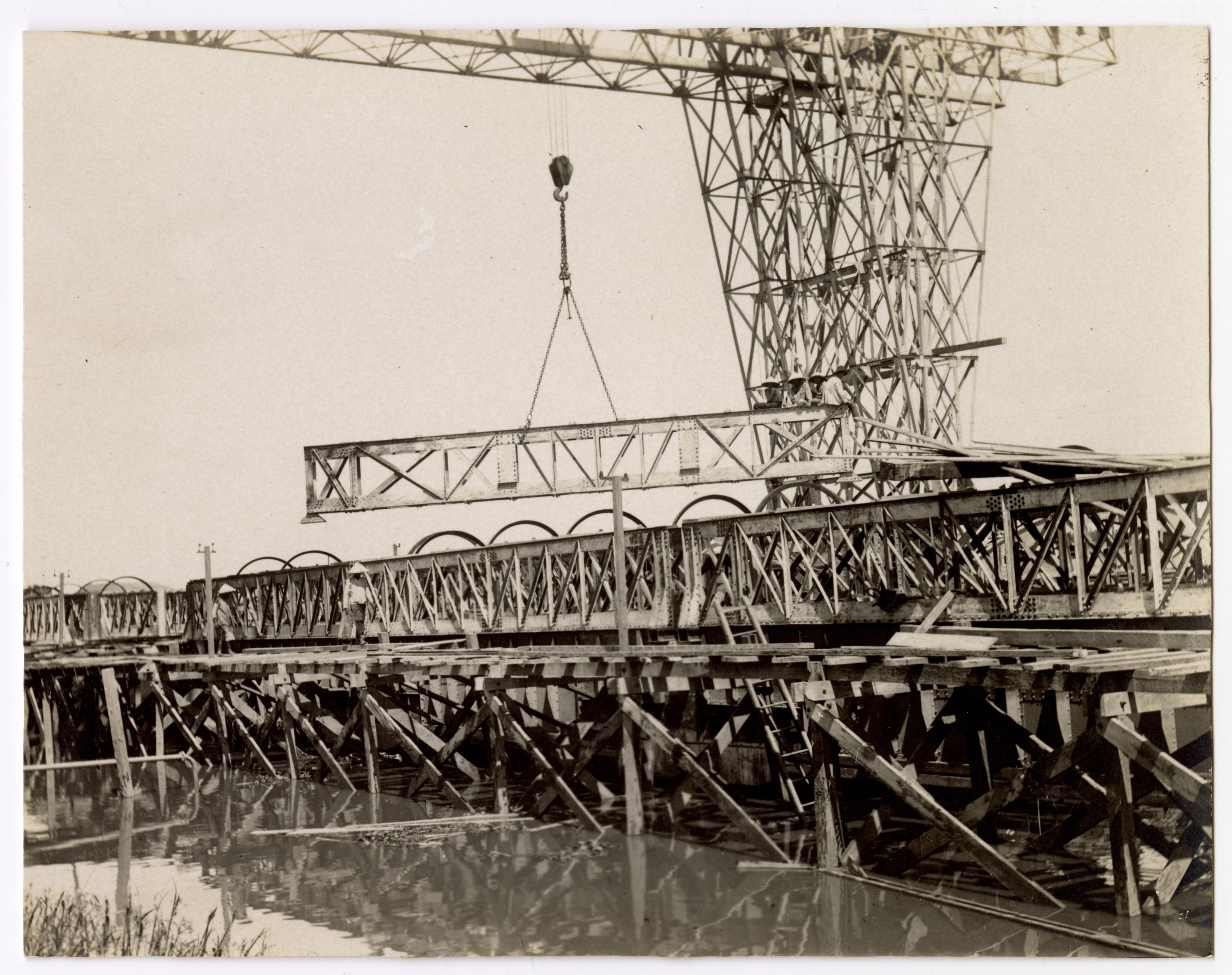 Photographie d'ouvriers indochinois et contremaîtres sur le chantier de construction d'un quai sur la rive droite de la rivière de Saigon, 1907-1910 : pont roulant.