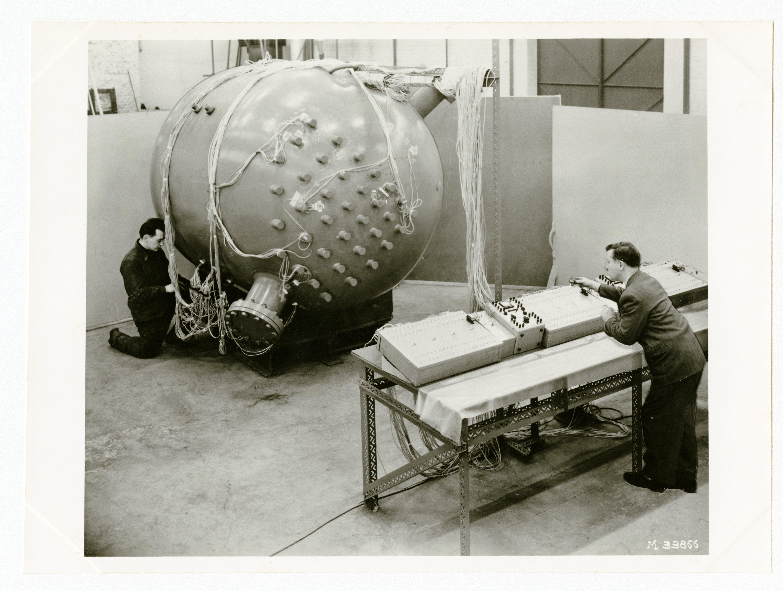 Vue de deux hommes travaillant sur une machine probablement expériementale.