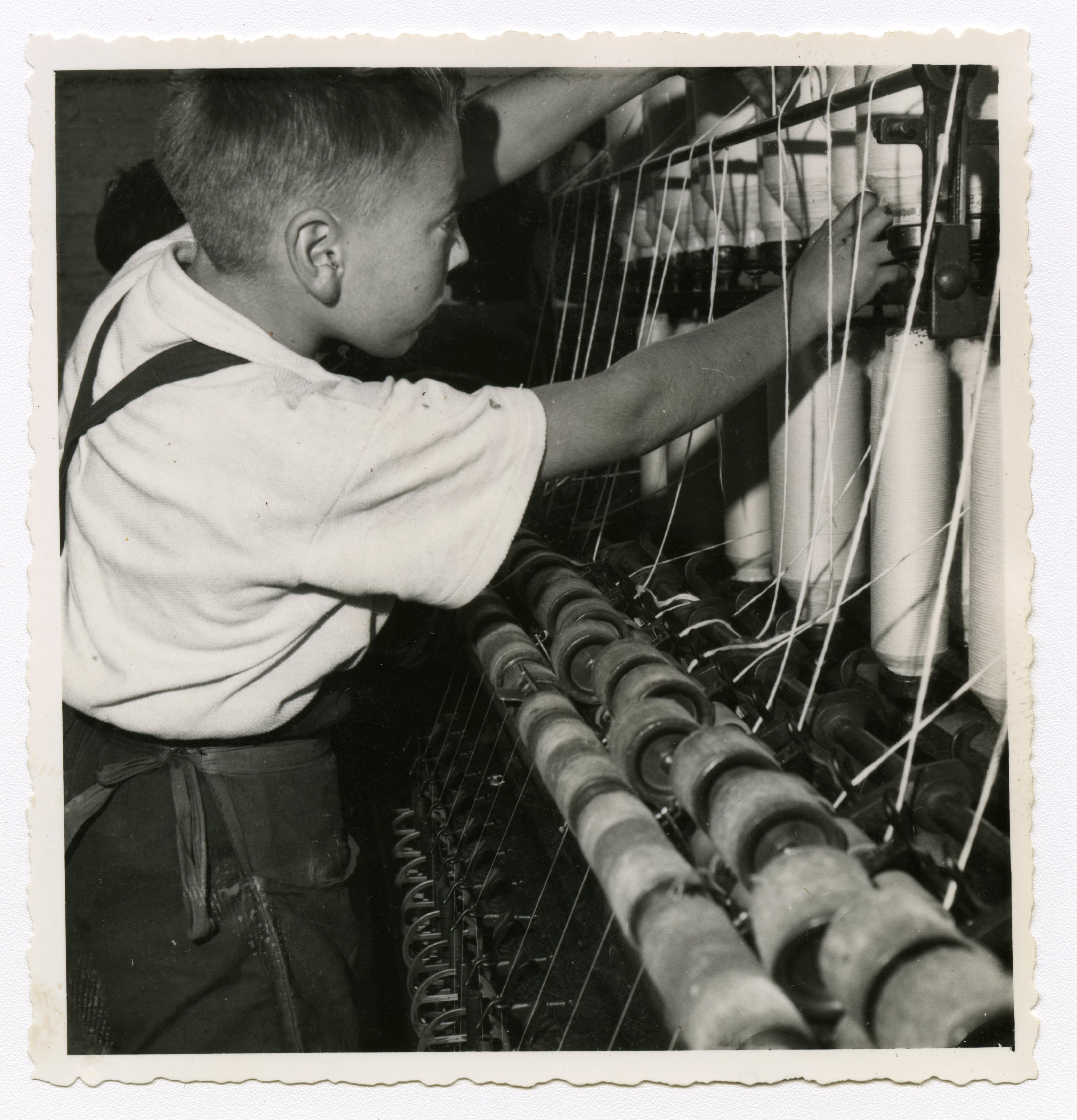 Jeune ouvrier travaillant sur un métier à tisser : tirage photographique, Lille (Nord), vers 1955.