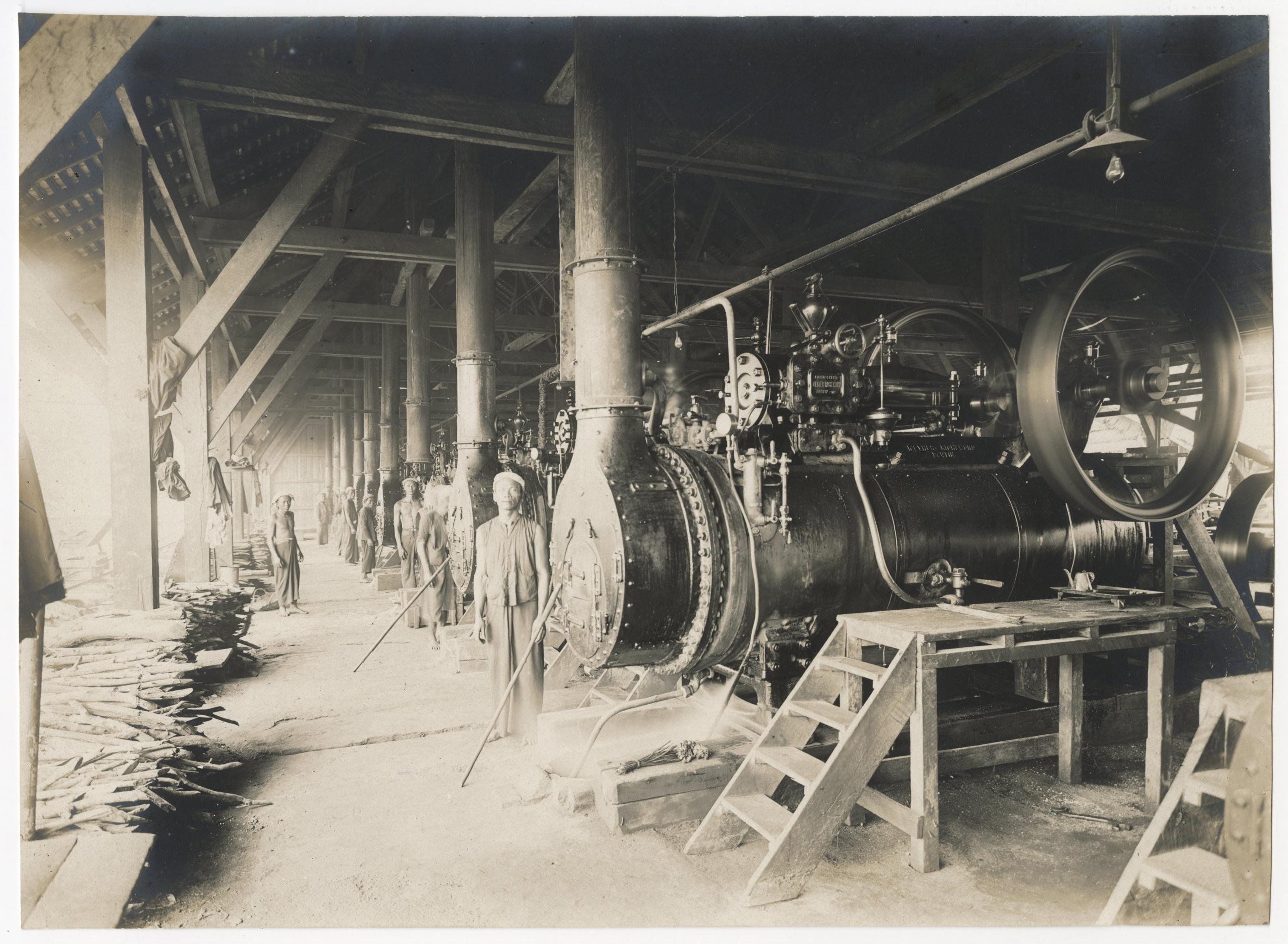 Photographie d'ouvriers indochinois et contremaîtres sur le chantier de construction d'un quai sur la rive droite de la rivière de Saigon, 1907-1910 : enlèvement des remblais et enrochements derrière le mur de quai.