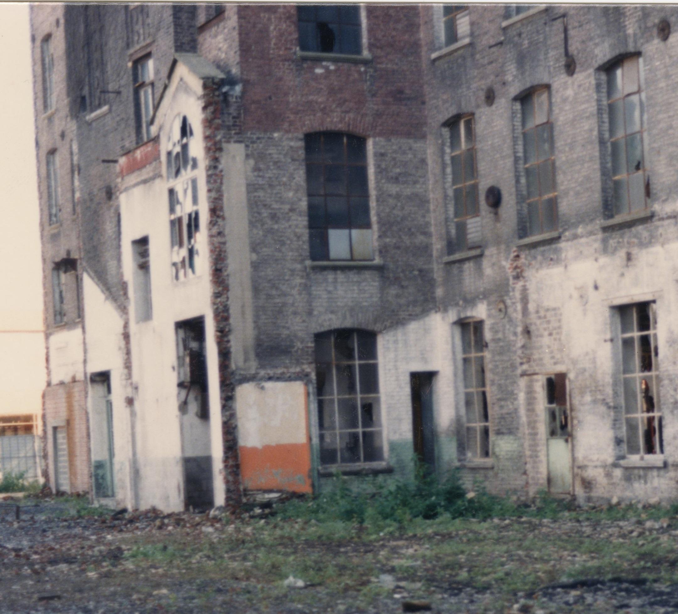 Photographie d'une façade de l'usine désaffectée, aux fenêtres cassées.