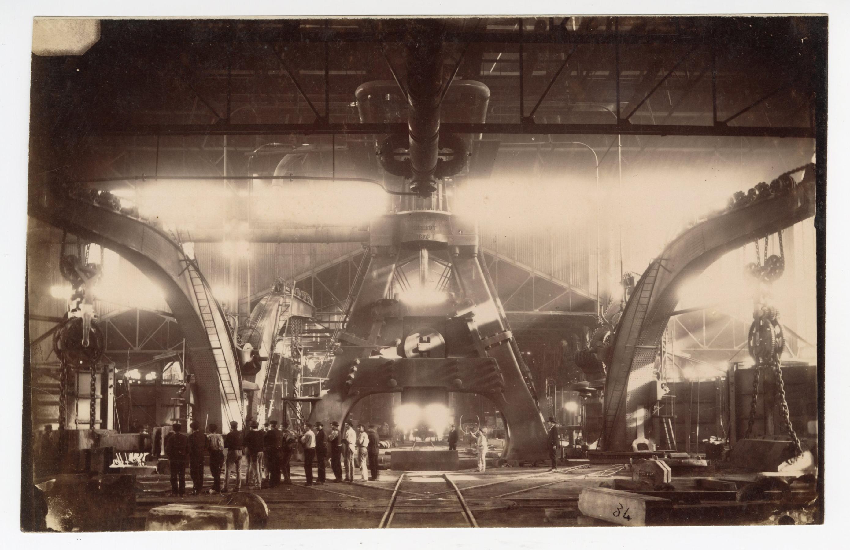 Travailleurs regroupés devant le marteau-pilon des aciéries Schneider : tirage photographique, Le Creusot (Saône-et-Loire), sans date.