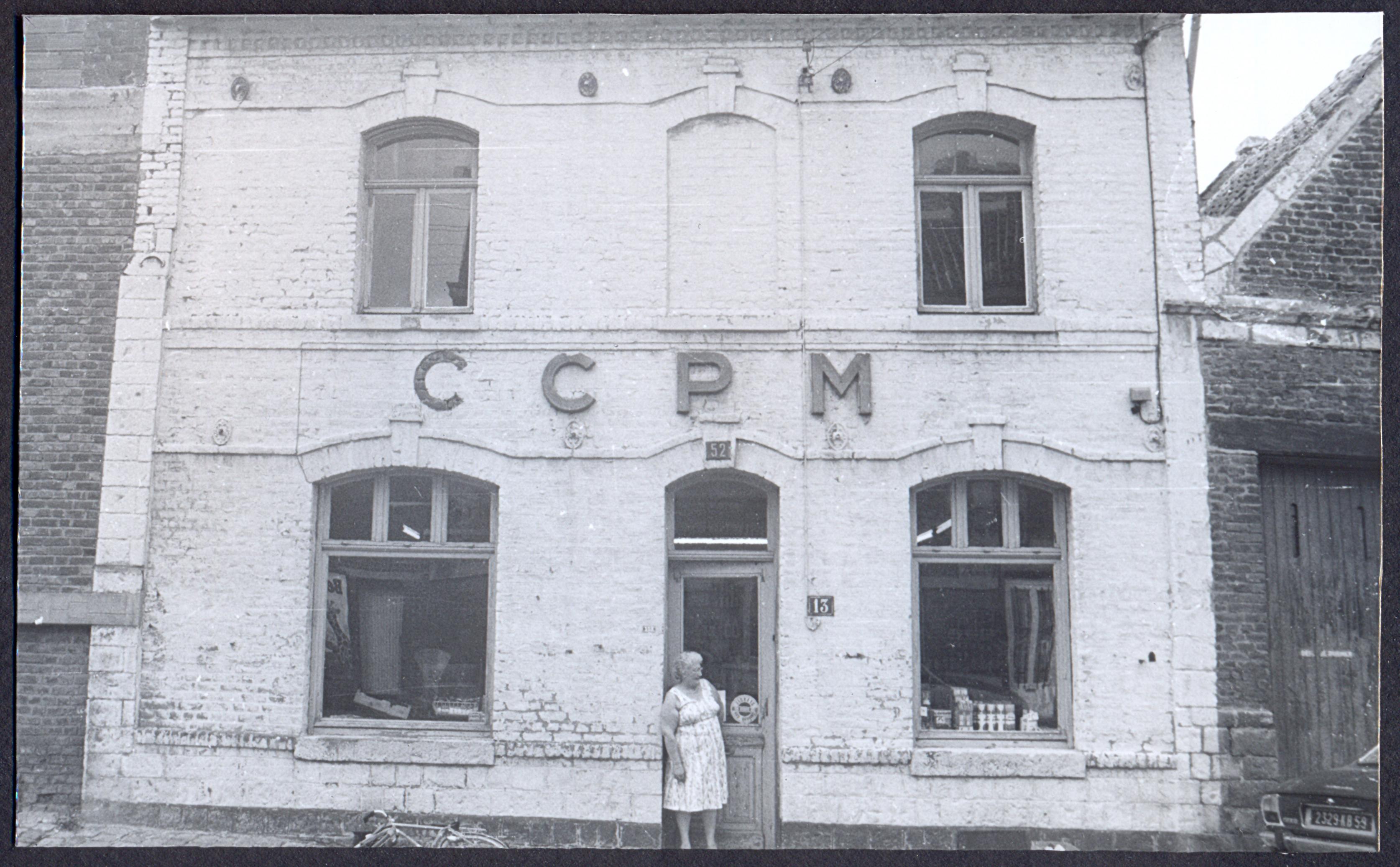 Commerçante posant devant la façade d'une coopérative minière : tirage photographique, Lewarde (Nord), 1982.