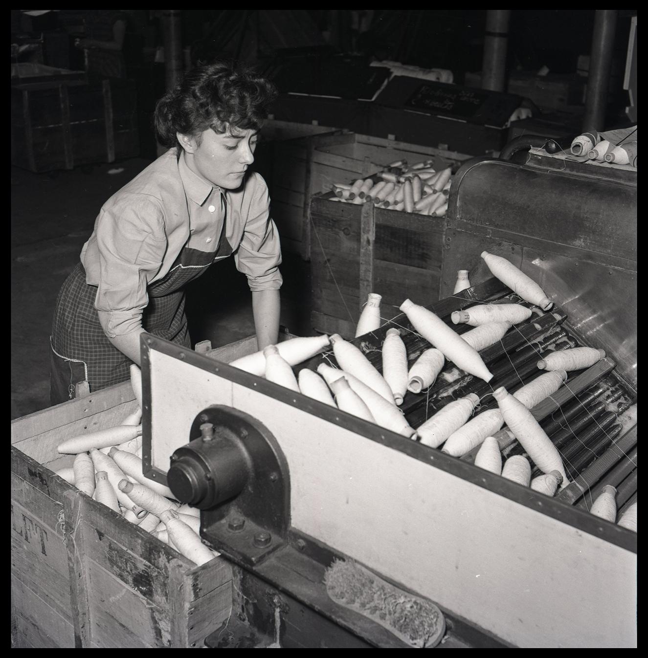 Ouvrière conditionnant des bobines de fils : tirage photographique, Lille (Nord), vers 1955.
