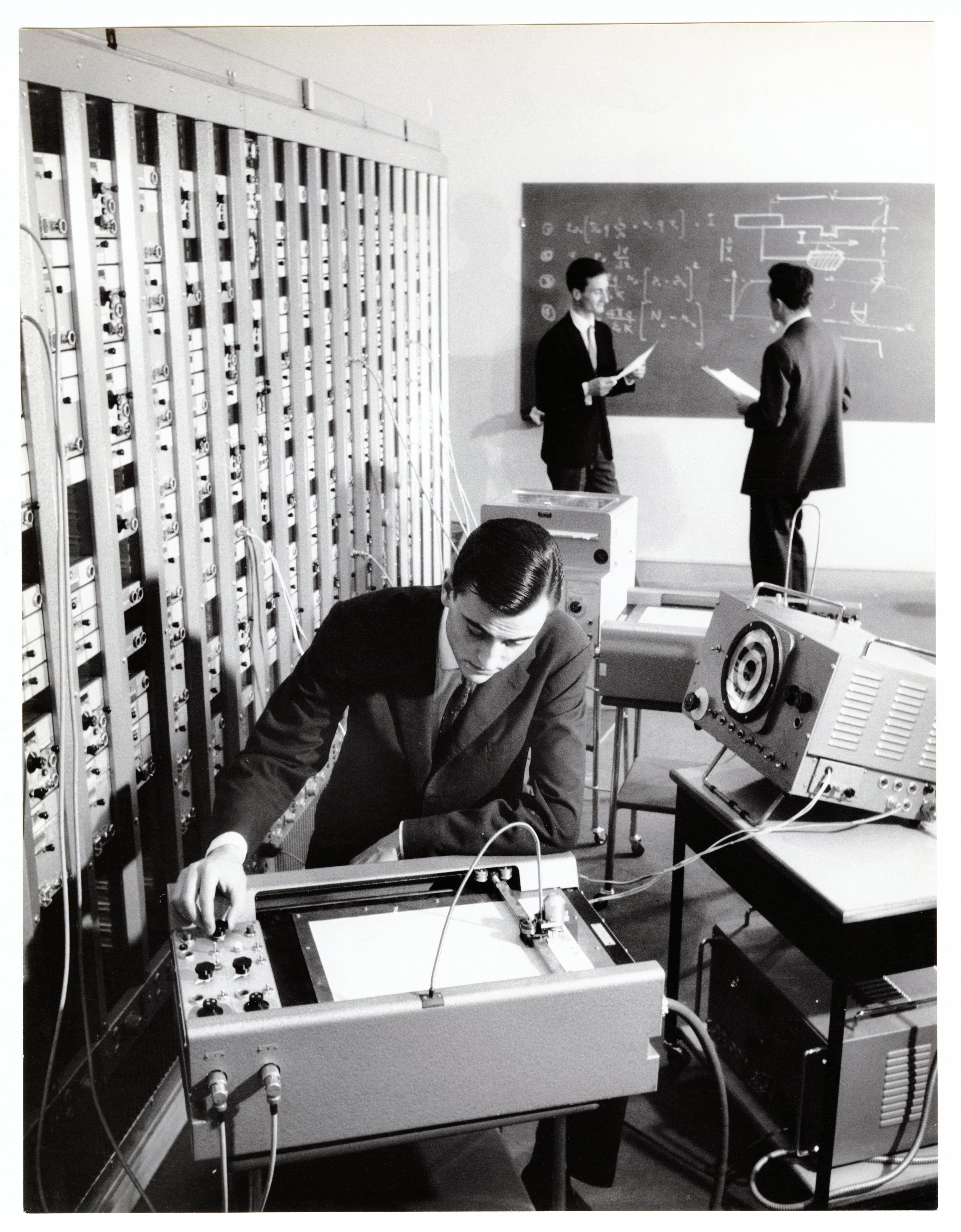 Ingénieur et physiciens participant au «Plan calcul» (plan gouvernemental destiné à rattraper le retard français en matière de nouvelles technologies) : tirage photographique, lieu inconnu, années 1960.