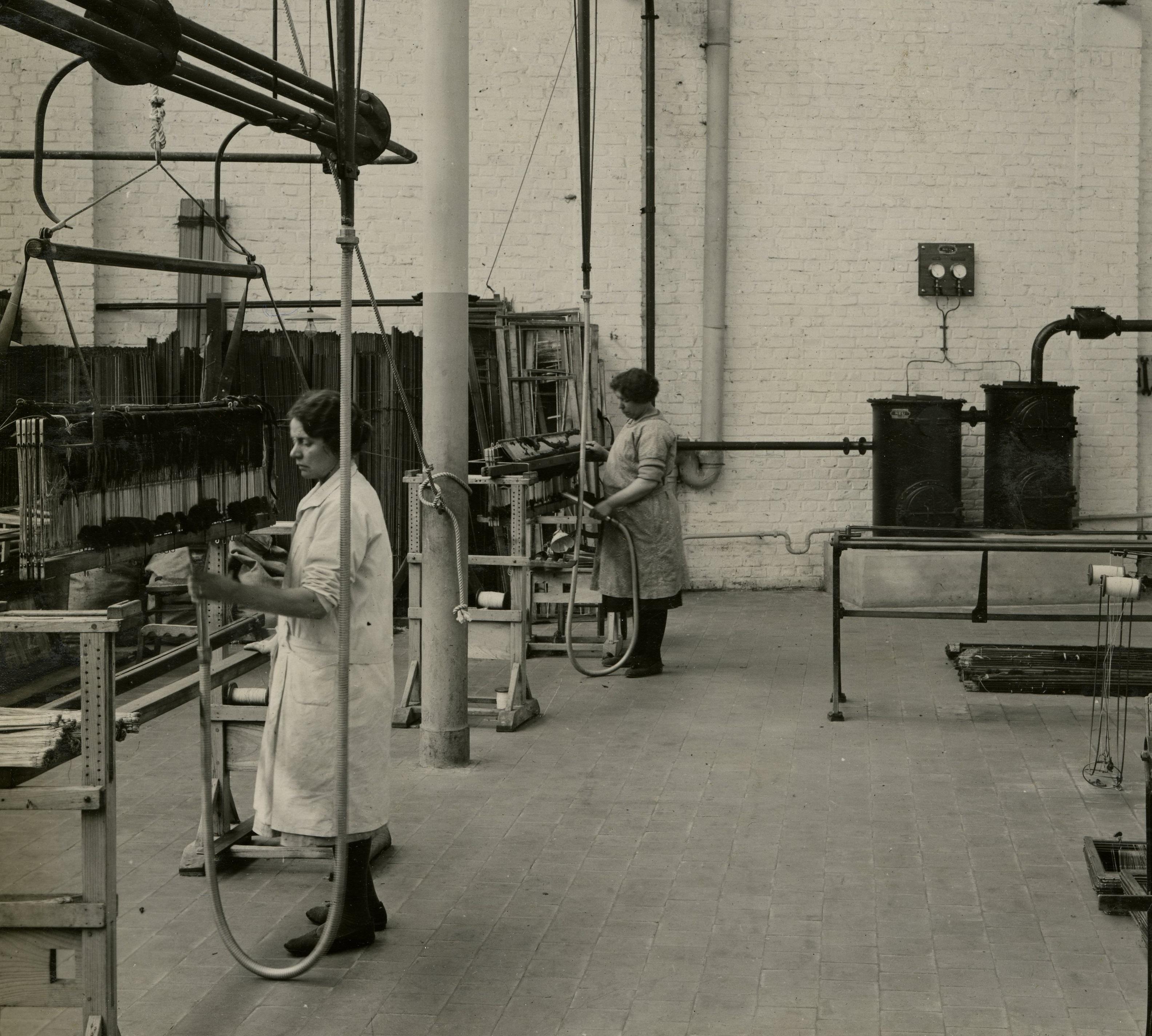Vue de deux femmes nettoyant des machines.