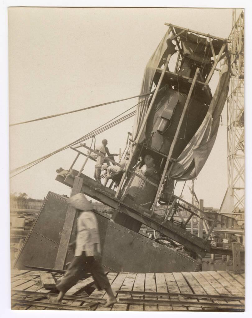 Photographie d'ouvriers indochinois et contremaîtres sur le chantier de construction d'un quai sur la rive droite de la rivière de Saigon, 1907-1910 : montage des caissons.