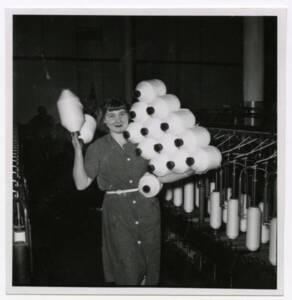 Une ouvrière textile pose avec ses bobines de fils, vers 1955.